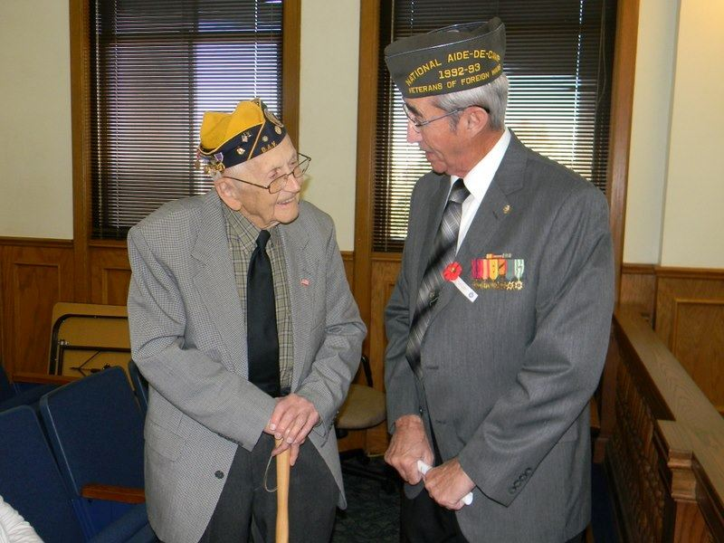 Two veterans, one with cane, both in grey suits, look and talk to one another inside court house